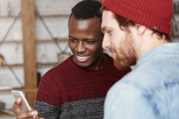Modern technology, people, leisure and online communication. happy young dark-skinned male holding cell phone and showing something to his stylish caucasian friend, both looking at screen and smiling