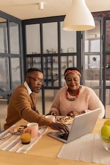 현대 기술. 그의 아내와 함께 앉아있는 동안 노트북의 버튼을 누르면 즐거운 수염 난 남자