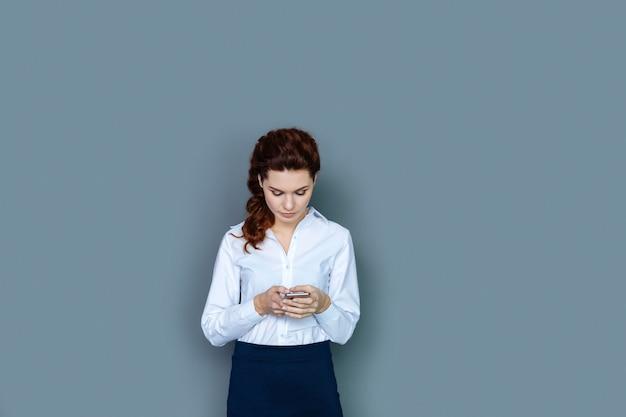 現代のテクノロジー。オフィスで働いている間彼女のスマートフォンを立って使用しているスマートで快適な素敵な実業家