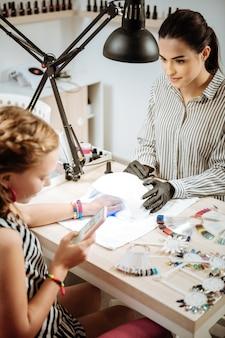 Modern teenager. modern cute stylish teenage girl using her smartphone while visiting nail artist