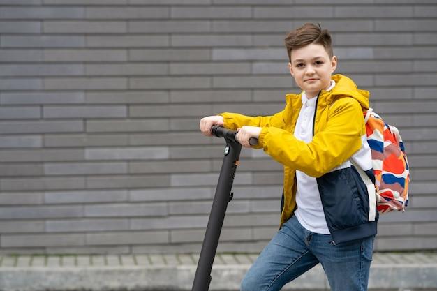 電動スクーターの現代のティーンエイジャー。 Premium写真
