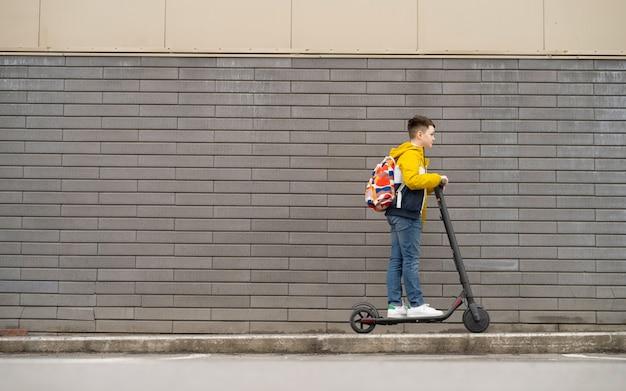 現代のティーンエイジャーは、レンガの壁の背景に電動スクーターに乗っています。