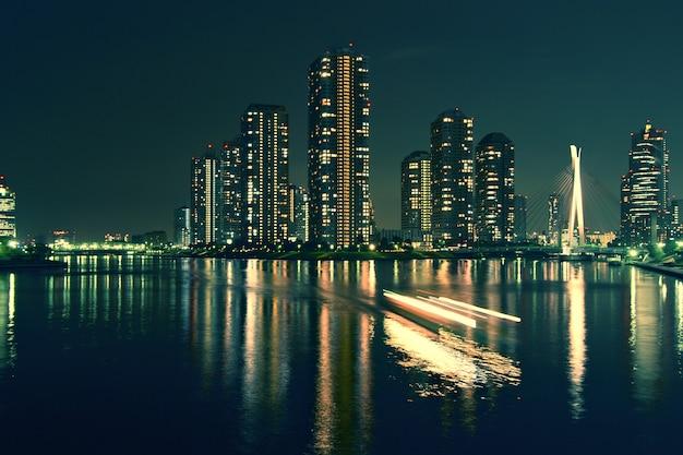 夜の水面反射と動く船の光跡のある現代の東京の建物、