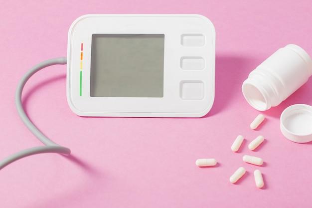Современный тонометр на розовой поверхности