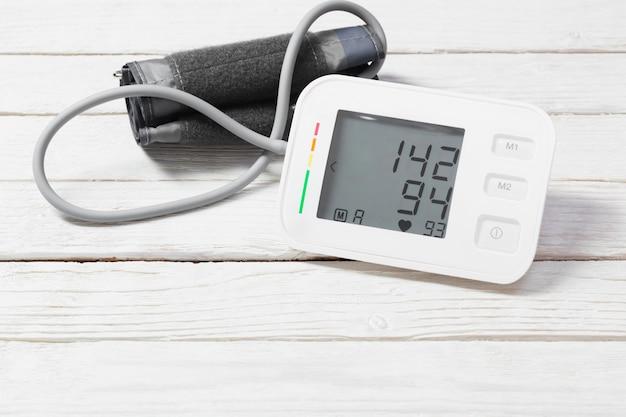 Modern tonometer on white wooden background