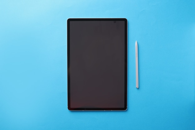 Modern touch tablet with stylus lies on blue background