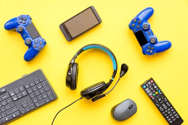 Современные игрушки - игровой контроллер, наушники, пульт от телевизора, смартфон и компьютерная клавиатура и мышь. игровые аксессуары виртуальной реальности.