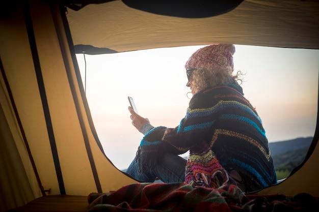 現代の旅行女性は、野生のテントの外でインターネット接続と携帯電話を使用しています-旅行とコミュニケーションの概念-無料の人々と代替の休暇
