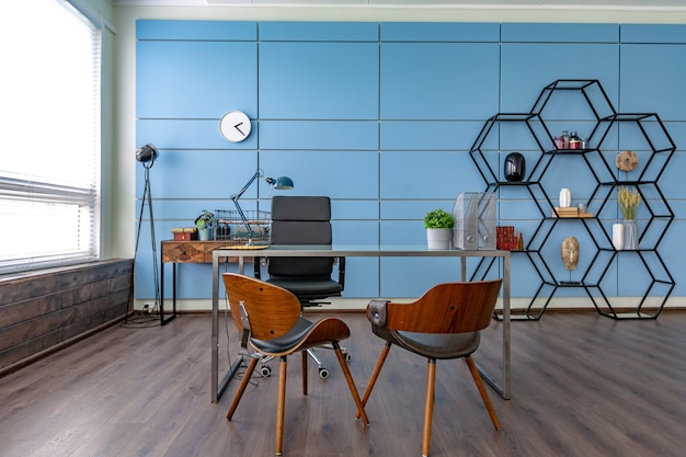 큰 창문과 일광이있는 파란색과 베이지 색의 미니멀리즘 스타일의 개인 스튜디오 사무실의 현대 유행 창조적 인 디자인