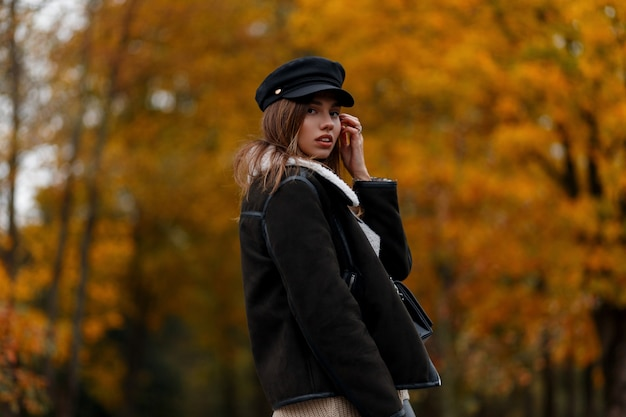 森の中の金の葉を背景に暖かい茶色のスタイリッシュなジャケットのバイザーと黒い帽子の現代のトレンディなヨーロッパの若い女性。ファッショナブルな女の子。女性のカジュアルアウターの新しいコレクション