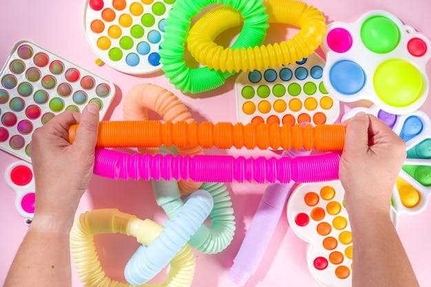 현대적인 트렌디한 아이들은 손가락 장난감을 만지작거리고 휴식을 취하는 개념 - 여성의 손은 흰색 배경, 위쪽 뷰 복사 공간에서 다른 밝은 팝-잇, 단순한 보조개, 퀴시, 팝 튜브를 가지고 노는 것입니다.