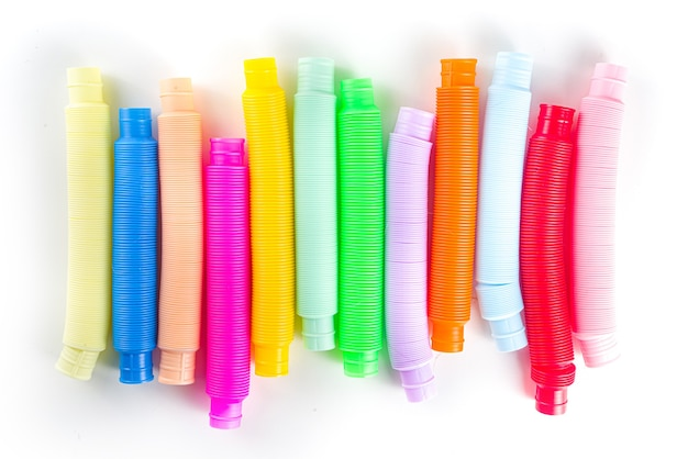 현대적인 트렌디한 아이들은 손가락 장난감을 만지작거리며 휴식을 취하는 개념 - 흰색 배경에 있는 다양한 밝고 화려한 팝 튜브 세트, 위쪽 뷰 복사 공간