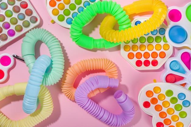 현대적인 트렌디한 아이들은 손가락 장난감, 휴식 개념 - 다양한 밝은 팝-잇, 단순한 보조개, 스퀴시, 팝 튜브, 화려한 분홍색 배경, 위쪽 뷰 복사 공간