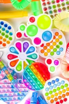 현대적인 트렌디한 아이들은 손가락 장난감, 휴식 개념 - 다양한 밝은 팝-잇, 단순한 보조개, 스퀴시, 팝 튜브, 흰색 배경, 위쪽 뷰 복사 공간