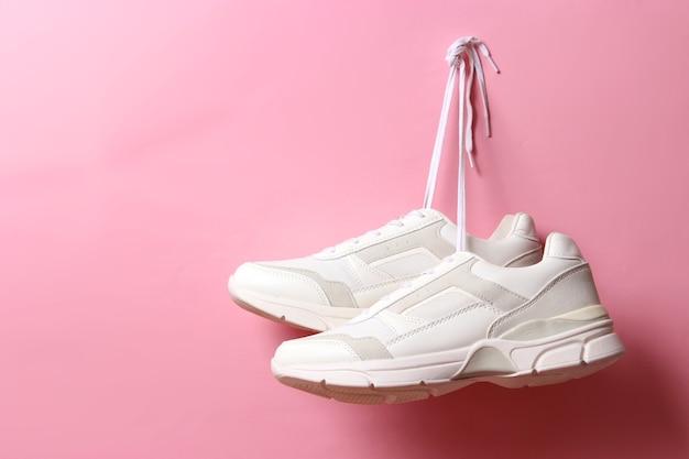 モダンなトレンディなスニーカーは、色付きの背景の靴ひもに掛かっていますカジュアルシューズスポーツシューズ