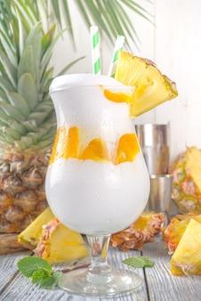 현대 열대 용암 흐름 칵테일. 나무 배경에 파인애플, 럼, 코코넛 크림과 함께 달콤하고 맛있는 여름 음료
