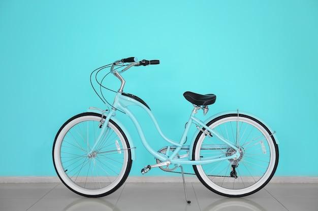 Современный двухколесный велосипед в помещении возле цветной стены