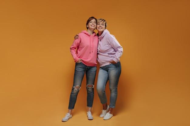 넓은 분홍색 후드, 스키니 청바지 및 흰색 운동화에 멋진 짧은 헤어 스타일을 가진 현대 두 여성이 카메라를보고 웃고 있습니다.