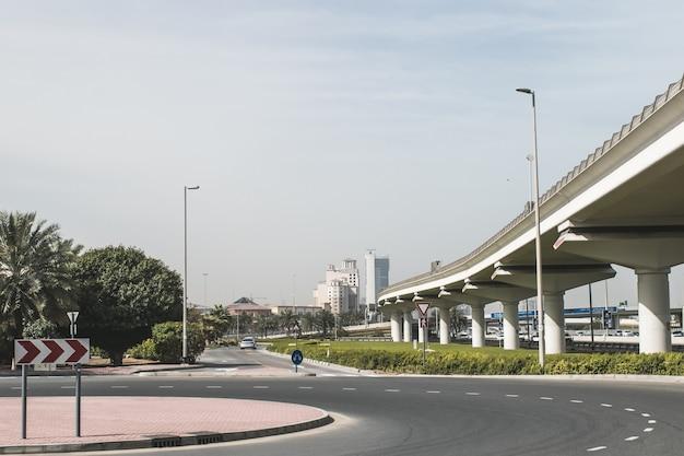 青い空と高速道路道路のあるモダンなuaeドバイ都市景観建築建設ビル