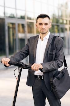 Современный городской альтернативный транспортный портрет уверенного бизнесмена, стоящего с электросамокатом