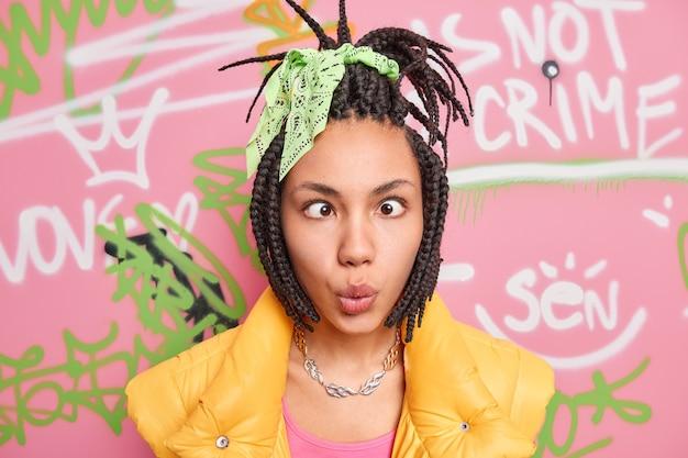 現代の都会の女の子は面白いしかめっ面をします目を交差させますドレッドヘアを持っています暗い肌は描かれた落書きの壁に立ち向かいます