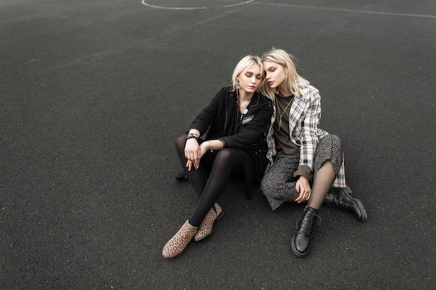 Modern urban twin sisters in beautiful casual wear sits on playground in city