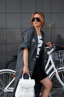 Современная городская молодая женщина в солнечных очках в длинной куртке с рюкзаком в футболке идет по улице возле серого здания. красивая девушка стоит возле старинных велосипедов на открытом воздухе. здоровый образ жизни.