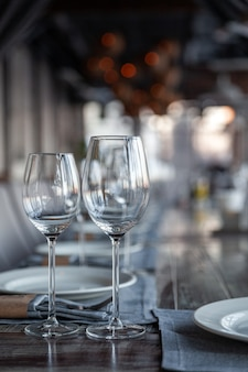 モダンなベランダレストランのインテリア、宴会、ワインとウォーターグラス、プレート、フォークとナイフ、テキスタイルナプキン。コンセプトバンケット、誕生日、会議、グループランチ、バーティカル、コピースペース