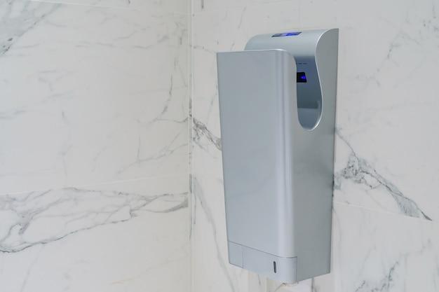 Modern vertical hand dryer in public restroom wc