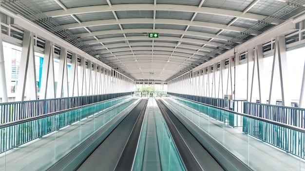 에스컬레이터의 현대 보도는 국제 공항에서 앞으로 이동하고 에스컬레이터는 뒤로 이동합니다.