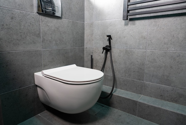Modern wall mounted toilet or water closet with lid closed in a tiled bathroom with monochrome grey decor in a close up corner view