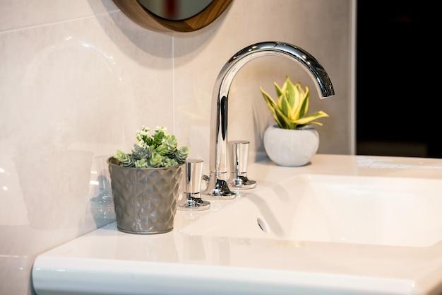 Modern washbasin with mixer tap in bathroom