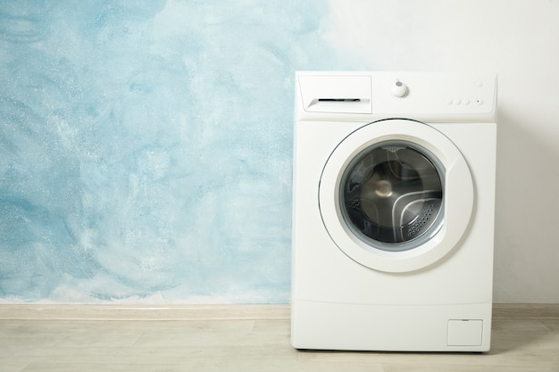 Modern washing machine against blue, space for text