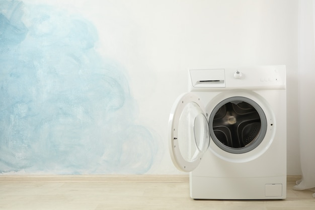 Modern washing machine against blue wall, space for text