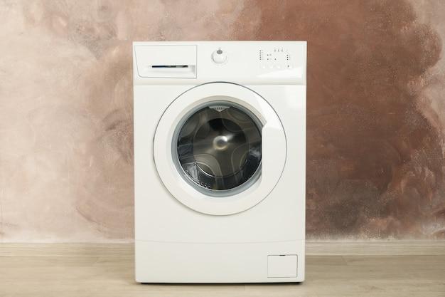 茶色の壁、テキスト用のスペースに対してモダンな洗濯機
