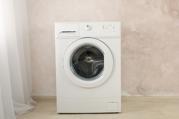 Modern washing machine against brown wall, space for text