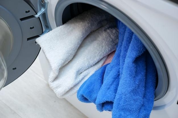 ドラムの洗濯物の山と開いたドアの上面図を備えたモダンな洗濯機