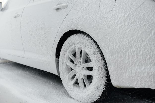 Современная мойка автомобильных колес пеной и высоким давлением воды. автомойка.