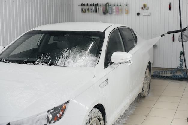 Современная стирка пеной и водой под высоким давлением белого авто. автомойка.