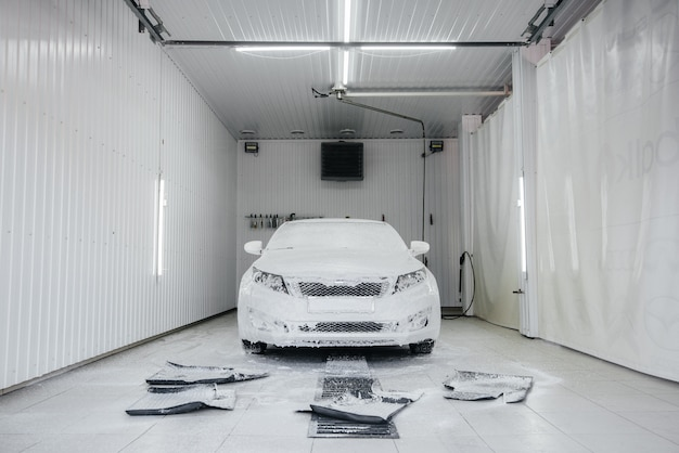 Modern washing with foam and high-pressure water of a white car. car wash.