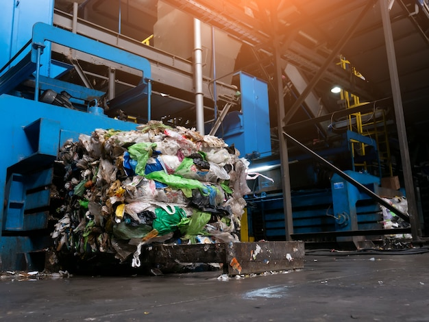 Modern waste sorting and recycling plant, hydraulic press makes wired bale from pressed pet bottles for processing and reuse of plastic. concept of defence of environment by materials recycle.