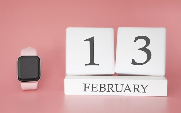 Современные часы с кубом календарем и датой 13 февраля на розовом фоне. концепция зимнего отдыха.