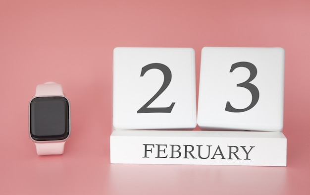 Современные часы с кубом календарем и датой 23 февраля на розовом фоне. концепция зимнего отдыха.
