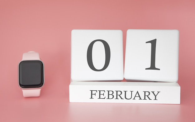 Modern watch with cube calendar and date 01 february on pink background. concept winter time vacation.