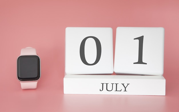 Modern watch with cube calendar and date 01 july on pink wall. concept summer time vacation.