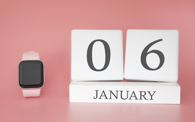 Modern watch with cube calendar and date 06 january on pink background. concept winter time vacation.