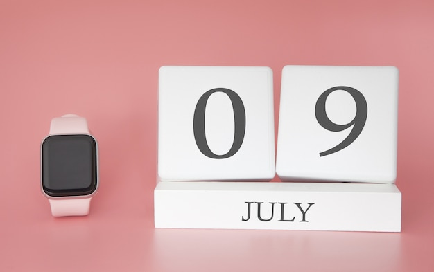 Modern watch with cube calendar and date 09 july on pink wall. concept summer time vacation.