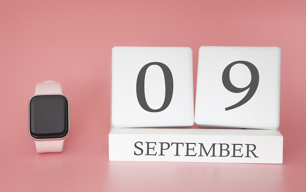 Modern watch with cube calendar and date 09 september on pink wall. concept autumn time vacation.
