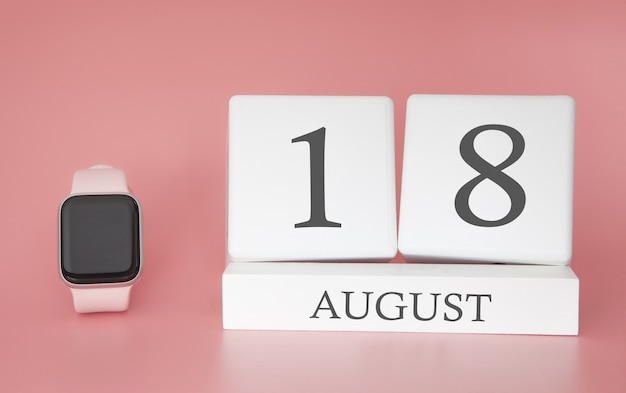 Modern watch with cube calendar and date 18 august on pink wall. concept summer time vacation.