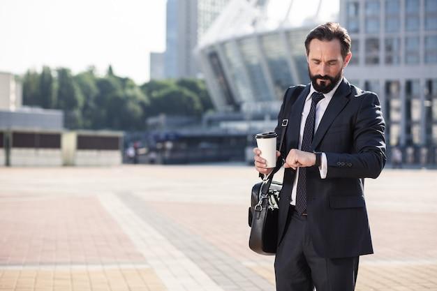 現代の生き方。街に立っている間時間をチェックするプロのハンサムなビジネスマン
